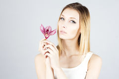 Beauty blonde with with pink flower in hand. Clear and fresh skin. Beauty face. Royalty Free Stock Image