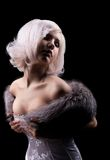Beauty blonde posing in corset and fur boa Stock Images