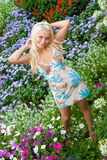 Beauty blonde stay near flower lawn Stock Photo