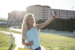 Beauty blonde woman taking self portrait. With arrow tattoo on arm royalty free stock image