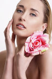 Beauty blonde young woman showing a fresh flower Royalty Free Stock Images