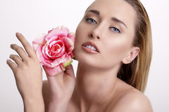 Beauty blonde young woman showing a fresh flower on white Royalty Free Stock Photography