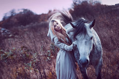 Beauty blondie with horse in the field,  effect Stock Images
