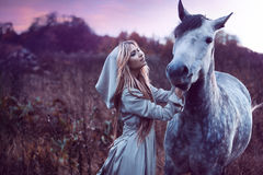 Beauty blondie with horse in the field,  effect Royalty Free Stock Photography