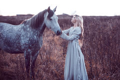 Beauty blondie with horse in the field,  effect Stock Photos