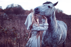 Beauty blondie with horse in the field, effect of toning. Portrait of a beauty blondie with horse royalty free stock photography