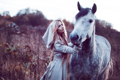 Beauty blondie with horse in the field, effect of toning. Portrait of a beauty blondie with horse royalty free stock images