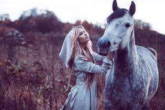Beauty blondie with horse in the field,  effect of toning Stock Photography