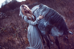 Beauty blondie with horse in the field, effect of toning stock photo