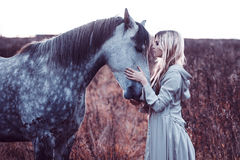 Beauty blondie with horse in the field Stock Photography