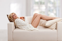 Beauty, blondie woman laying in a sofa. With an orange-colored cup Stock Image