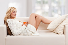 Beauty, blondie woman in a sofa. With an orange coloured cup Royalty Free Stock Photos