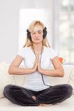 Beauty, blondie woman in a yoga position. Listening music with earphones Stock Photo