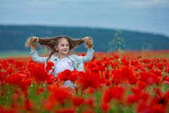 Beauty blue eyes teen enjoy summer days .Cute fancy dressed girl in poppy field. Field of blooming poppies royalty free stock images