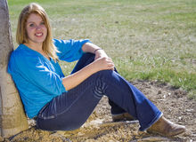 Beauty in Blue On the Farm. Beautiful young redhead relaxing on the farm Stock Images