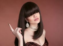 Beauty bob hair. Vogue Hairstyle. Fashion Manicure. Portrait of. Gorgeous young dark-haired woman. Sensual lips makeup. Golden polish manicured nails Royalty Free Stock Photos