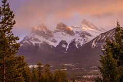 Beauty of Bow Valley mountains, Canmore, Canada. Sunset light and storm above Three sisters peak, in the fog, flurries in mountains stock image