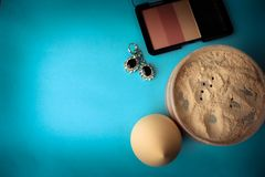 Beauty box, loose matte mineral powder and blush with a beauty blender for makeup and silver earrings on a blue background stock photos