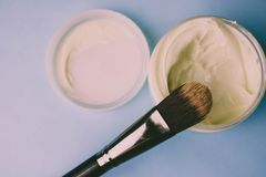 A beauty box with a wooden brush made from natural hard lint for a tone and a round jar of cream, a make-up base royalty free stock photo