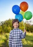Beauty boy with balloon outdoors Stock Photos