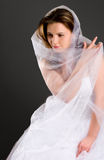 Beauty bride. Sitting beauty bride in white dress looks down isolated stock image