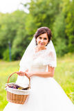 Beauty bride in bridal gown with basket on the nature. Beautiful model girl in a white wedding dress. Female portrait in Royalty Free Stock Image