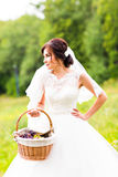 Beauty bride in bridal gown with basket on the nature. Beautiful model girl in a white wedding dress. Female portrait in Stock Images