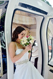 Beauty bride in bridal gown with bouquet and lace veil in the car. Beautiful model girl in a white wedding dress. Female portrait in the auto. Woman with Stock Images