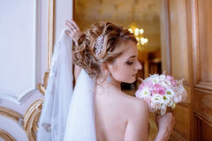 Beauty bride in bridal gown with bouquet and lace veil indoors. Beautiful model girl in a white wedding dress. Female portrait of cute lady. Woman with Royalty Free Stock Photo