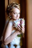 Beauty bride in bridal gown with bouquet and lace veil indoors. Beautiful model girl in a white wedding dress. Female portrait of cute lady. Woman with Stock Photo