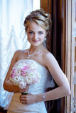 Beauty bride in bridal gown with bouquet and lace veil indoors. Beautiful model girl in a white wedding dress. Female portrait of cute lady. Woman with Royalty Free Stock Photography