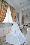 Beauty bride in bridal gown with bouquet and lace veil indoors. Beautiful model girl in a white wedding dress. Female portrait of cute lady. Woman with Stock Image