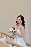 Beauty bride in bridal gown with bouquet and lace veil indoors. Beautiful model girl in a white wedding dress. Female portrait of cute lady. Woman with Royalty Free Stock Images