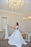 Beauty bride in bridal gown with bouquet and lace veil indoors. Beautiful model girl in a white wedding dress. Female portrait of cute lady. Woman with Royalty Free Stock Photos