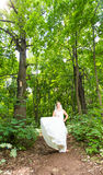 Beauty bride in bridal gown with bouquet and lace veil on the nature. Beautiful model girl in a white wedding dress Stock Photos