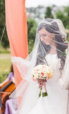 Beauty bride in bridal gown with bouquet and lace veil on the nature. Stock Photography