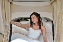 Beauty bride in bridal gown with lace veil in the car. Beautiful model girl in a white wedding dress. Female portrait in the auto. Woman with hairstyle. Cute Royalty Free Stock Images