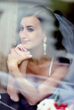 Beauty bride in bridal gown with lace veil indoors. Beautiful model girl in a white wedding dress. Female portrait of cute lady. Woman with hairstyle Royalty Free Stock Image