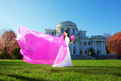 Beauty bride with a long purple veil Royalty Free Stock Photo