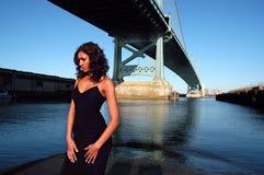 Beauty by the bridge. Beautiful model posing by Ben Franklin Bridge in Philadelphia royalty free stock images