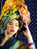 Beauty bright woman with creative make up, many shawls on head l Stock Images