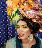 Beauty bright woman with creative make up, many shawls on head Stock Photos