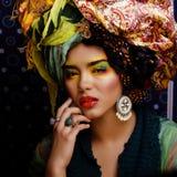 Beauty bright woman with creative make up, many shawls on head Stock Photography