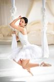 Beauty brunette ballerina on a swing in room Stock Photos