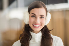 Beauty brunette with ear muffs smiling at camera Stock Photos
