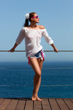 Beauty Brunette Girl in Denim Shorts. Seaside Holidays. Fashionable bronced woman in jeans shorts with pink suspenders and white shirt relaxing on the terrace Stock Photos