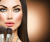 Beauty brunette girl with makeup brushes Royalty Free Stock Images