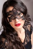 Beauty brunette with lace mask. A beauty young brunette with lace mask - female portrait stock photography