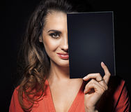 Beauty brunette hiding half of face behind black panel Royalty Free Stock Photos
