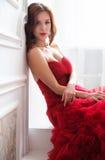 Beauty Brunette model woman in evening red dress. Beautiful fash Stock Photo